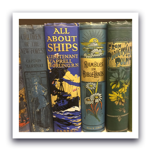A collection of antique hardback books. The colours are faded and the covers have started to fray a little.